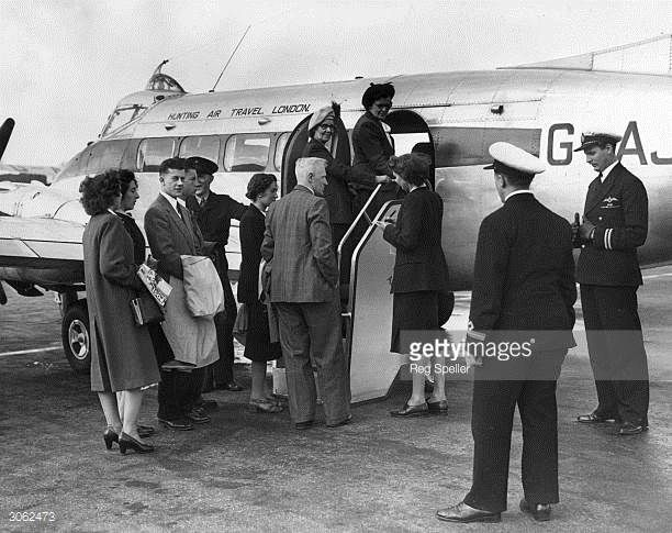 Tourists board a passenger plane at Croydon Airport south London bound for Jersey One woman carries a copy of Picture Post for the journey