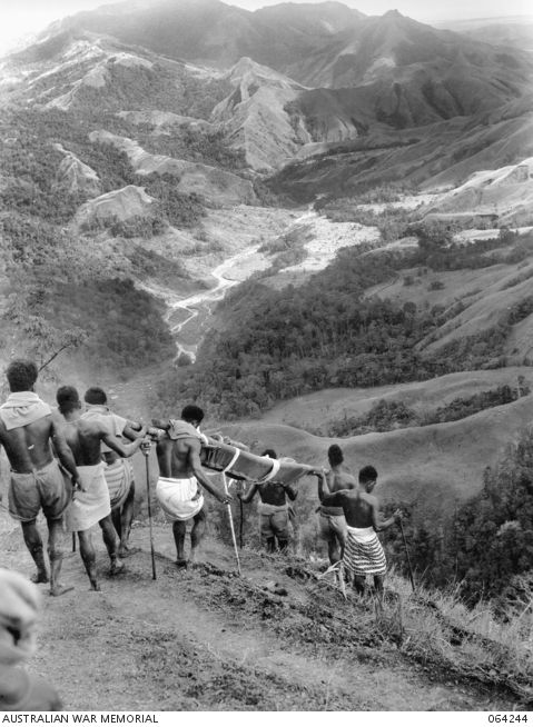 A New Guinean bearers carrying a stretcher down a steep slope from Shaggy             Ridge to a dressing station at Guy's Post. In the centre of             the photograph the Faria River runs into the Ramu Valley. Reference number 064244