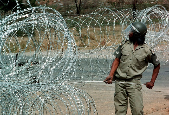 A paramilitary policemen with the Ciskeien homeland security forces erests a razor wire barricade on the border with South Africa September 7, 1992.  Twenty nine ANC supporters were killed when security forces opened fire after the marchers broke through the border in an attempt to march on aforce the Ciskeien military leader Brigadier Oupa Gqozo to allow free political activity in Ciskei. (Greg Marinovich)