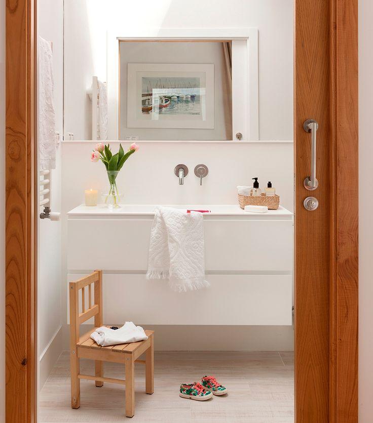 Baño con bajolavabo volado en blanco sin tiradores, espejo, silla de niño y puerta corredera de madera