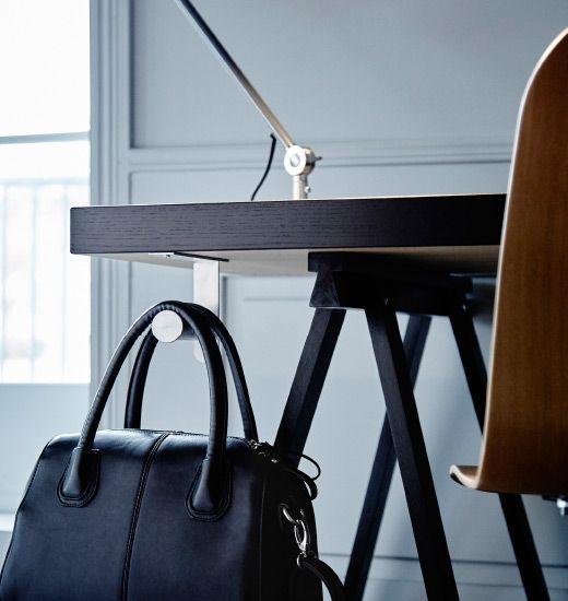 Un porte-rouleau WC IKEA GRUNDTAL est fixé en dessous d'un bureau. Un sac à main y est accroché.