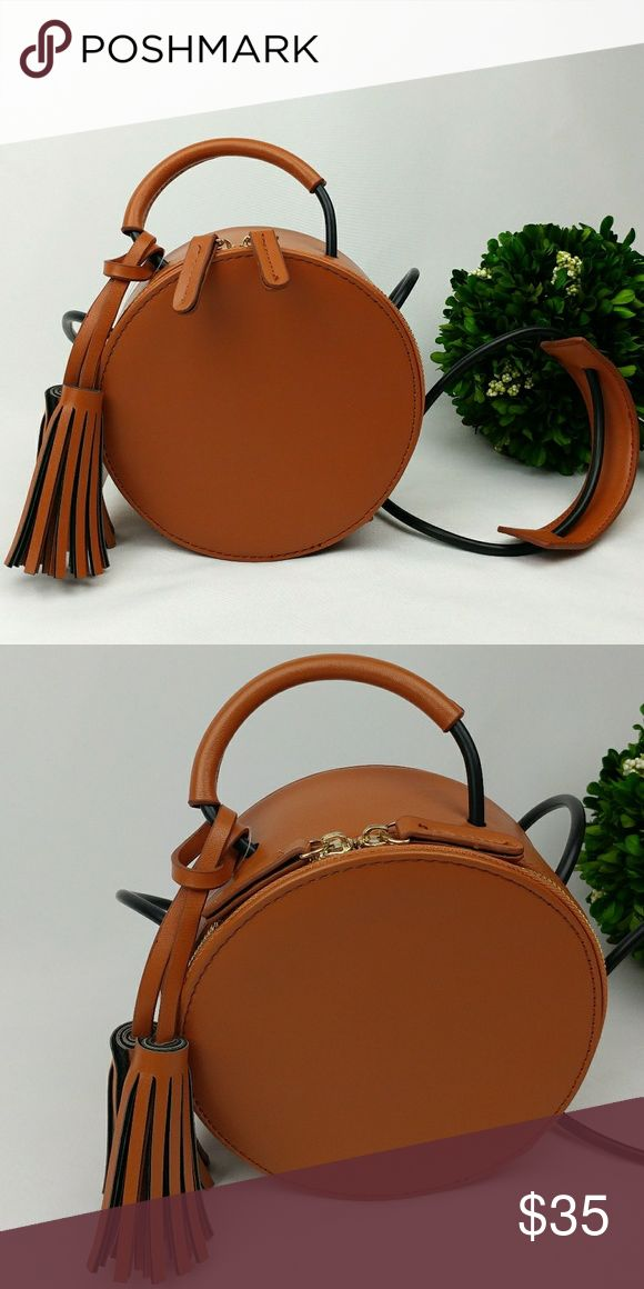 """HPNWT MELIE BIANCO VEGAN LEATHER ROUND CROSSBODY Premium vegan leatherpetite crossbody comes in a fun round shape with side tassels. May also use as a handle bag, retractable straps. Featuring a zipper top closure, an inner slim pocket, and a fully lined interior.  Dimensions: 6.5""""L x 3""""W x 6.5""""H; 36""""handle drop Has a two very light thin scratches( pictured) Melie Bianco Bags"""