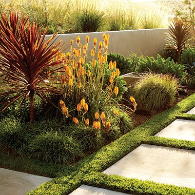 Orange and red plants line the walkway low mounding grasses, such as Carex glauca, and perennials like Sedum 'Autumn Joy'. Sunset magazine