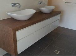 Bathroom vanity by East Coast Kitchens and Bathrooms- Installed with NAV Navurban™  Coolum Spotted Gum decor, finger pull with shadow line 60mm mitred edge with grain matching waterfall gable.