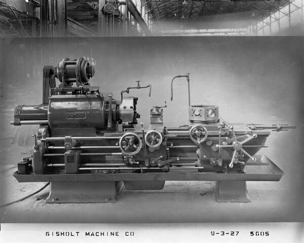 "Automatic saddle lathe in the factory shop. Promotional material for the Gisholt Machine Company states that ""for duplication of machined castings and forgings in large quantities, the Gisholt Automatic Turret Lathe is even more rapid than the hand operated machine, and its assembly of multiple cutting tools do their work more quickly and surely."" Generally one operator ran three or more machines, ""reducing the cost for labor to a fraction of that required for hand operated mac..."