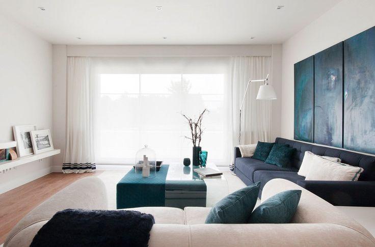 Soggiorno contemporaneo moderno, con grandi finestre, in colori bianco e blu. Seria di quadri astratti di grandi dimensioni, colore blu.