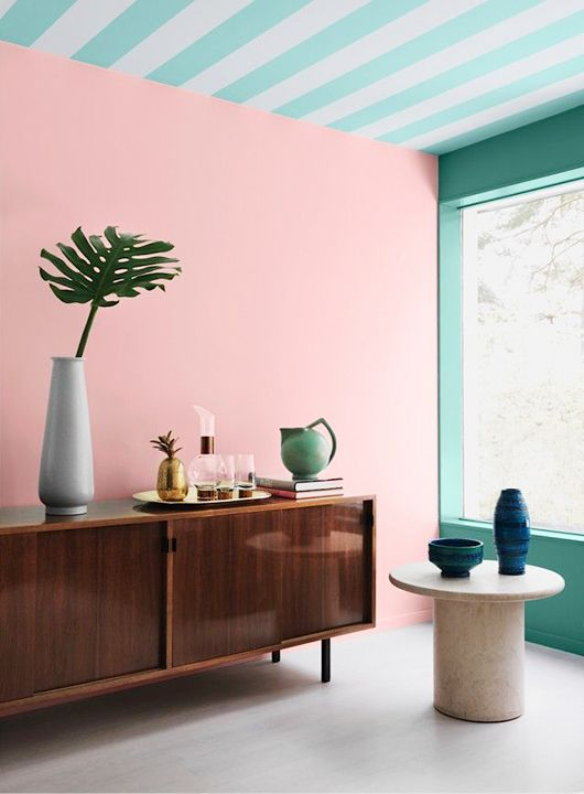 The dark wood sideboard and table are the perfect juxtaposition to the pastel pink and teal stripes in this room