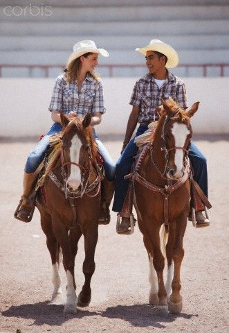 Couple in cowboy hats riding horses