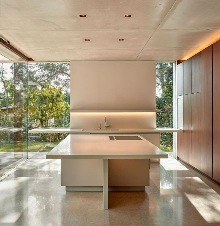 In this minimalist kitchen, floor-to-ceiling windows provide ample natural light, while a square kitchen island creates plenty of space for food preparation.
