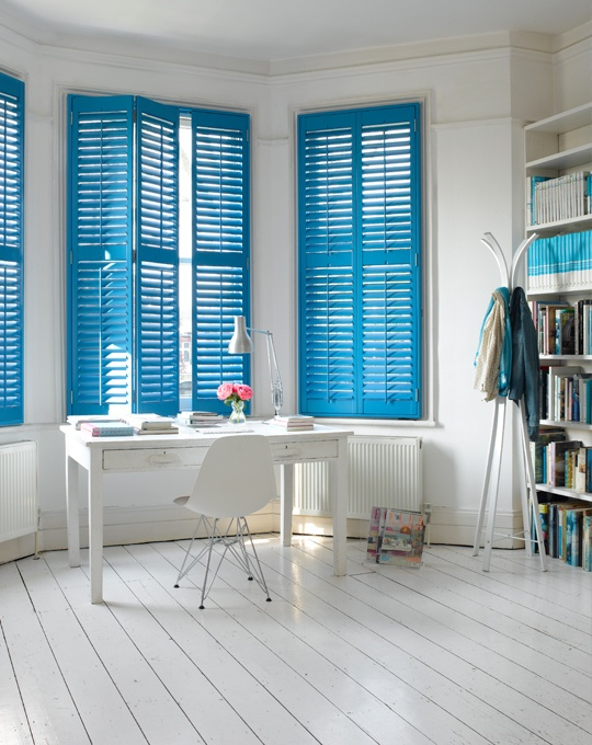 Even though I LOVE white shutters, painting them a bright, bold color is a great idea.  Nice home office space.