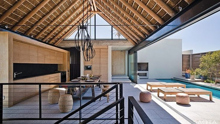 Indoor/outdoor kitchen and dining room in a home in Shelley Point, South Africa designed by SAOTA