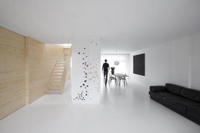 un revêtement de sol en résine blanche dans le salon spacieux avec un canapé noir