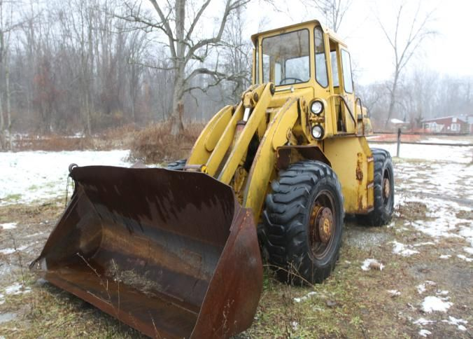 Yellow Trojan loader model 1900 with a V-8 Cummins motor, runs and works. Hour meter reading 9,198. Located at property 3.