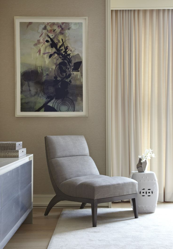 This soft gray living room features an elegant and contemporary style, with angular furniture, abstract artwork, and a ceramic stool acting as an end table.