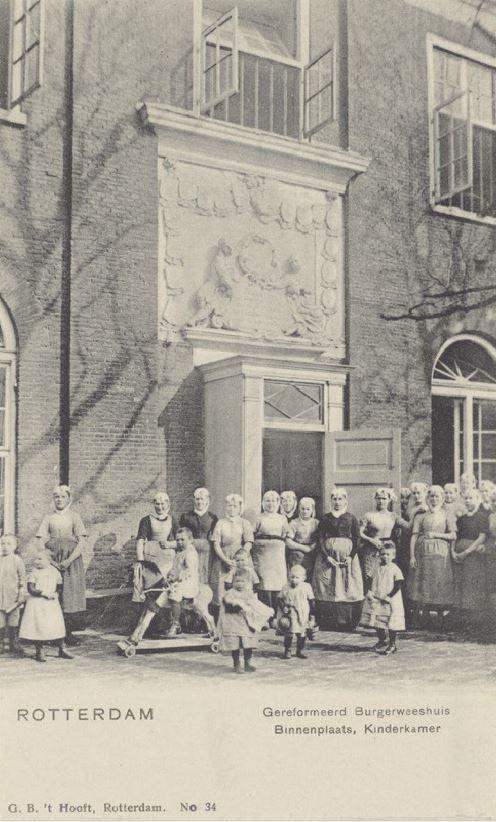 Personeel en weeskinderen van het Gereformeerd Burgerweeshuis aan de Goudsewagenstraat, voor de ingang van de kinderkamer, vanaf de binnenplaats. Rotterdam 1900 #ZuidHolland #Rotterdam #wezen #gereformeerd