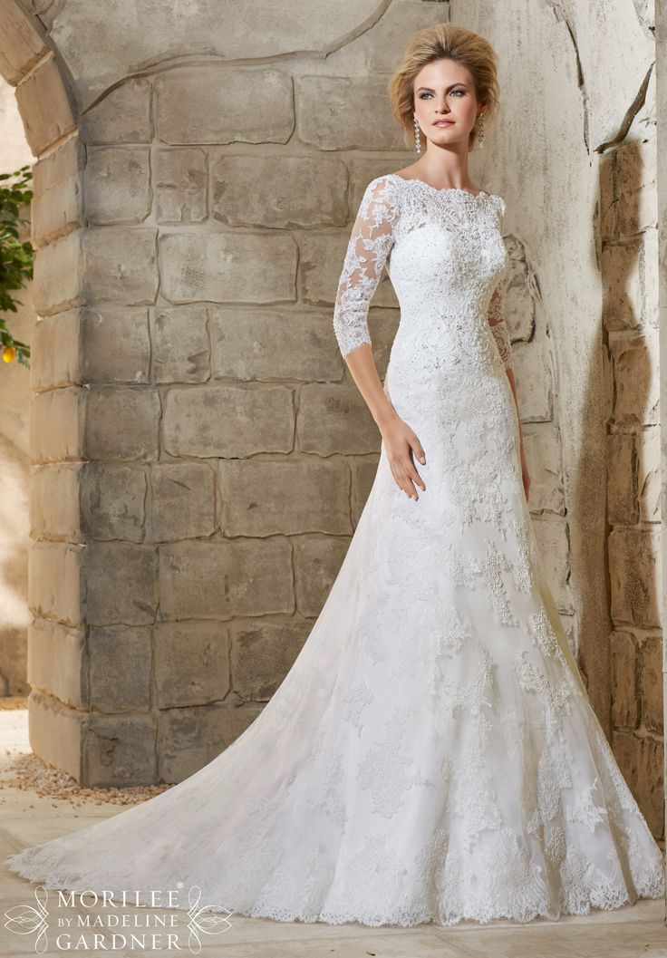 "Wedding Dresses and Wedding Gowns by Morilee featuring Allover Alencon Lace Gown with Delicate Crystal Beading and Scalloped Hemline This classic lace wedding gown features a beautiful scalloped bateau neckline, delicate sleeves, and deep V back. Available in Three Lengths: 55"", 58"", 61"". Colors Available: White, Ivory"