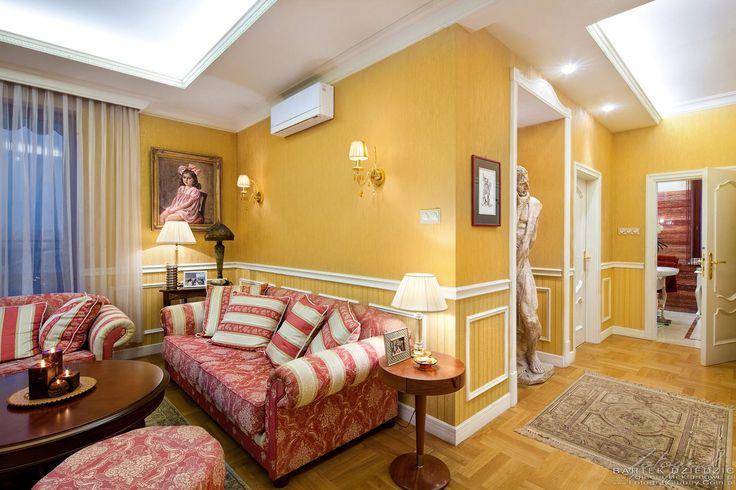 Fotograf do zdjęć apartamentu w Krakowie. Zdjęcie salonu w tyle widoczne wejście do łazienki i hol z rzeźbą człowieka.