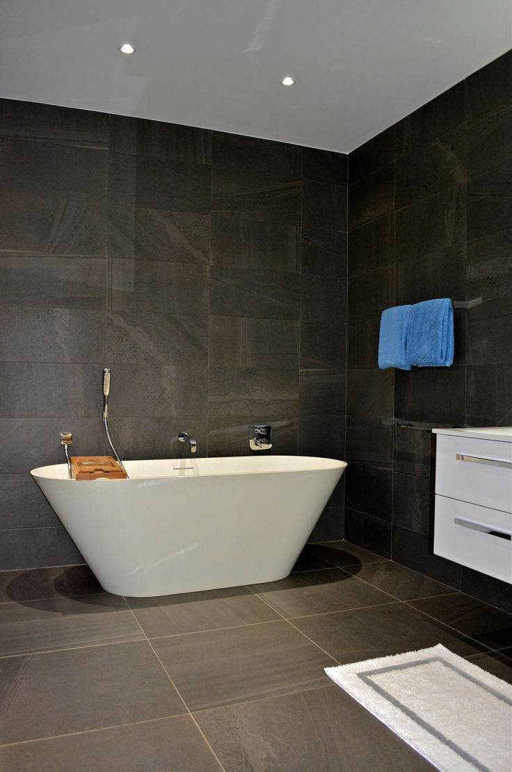 Bathroom with grey stone tiles and free standing bath.