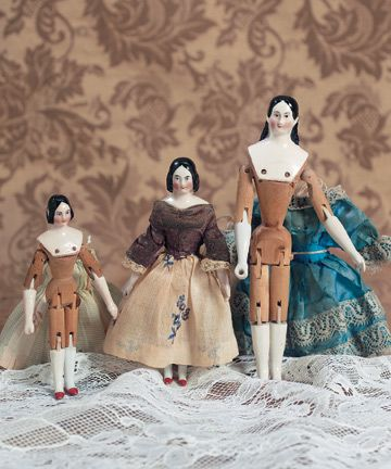 ~~Lovely wooden bodies~~  Pink-tinted porcelain shoulderhead with centerpart and long fingercurls, painted blue eyes, red and black upper eyeliner, single stroke brows, closed mouth, rosy cheeks, wooden articulated body with dowel-jointing at shoulders, elbows, hips and knees, porcelain forearms and lower legs, painted orange shoes, antique costume.