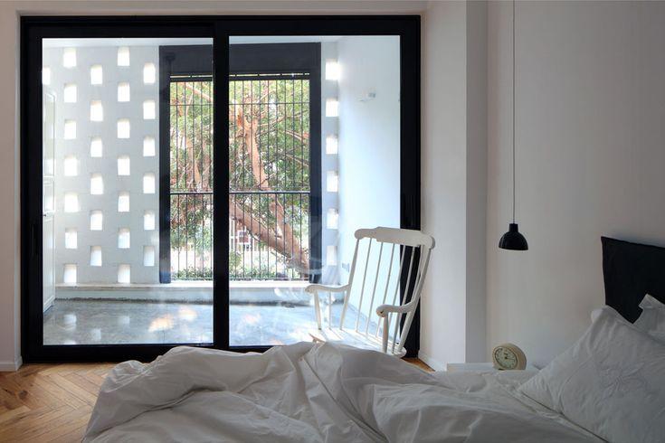 חדר ההורים נזירי כמעט, עם מעט רהיטים וסקלת צבעים של שחור-לבן ועץ. חלון זכוכית גדול מפריד בין החדר למרפסת חצי סגורה, שצופה לרחוב קטן שיוצא מהשדרה. האור מסונן באמצעות קיר לבנים במראה שתי וערב, שאופייני לבנייה התל אביבית של שנות ה-50 ולוקח השראה מהמשרבייה האסלאמית  ( צילום: עוזי פורת )