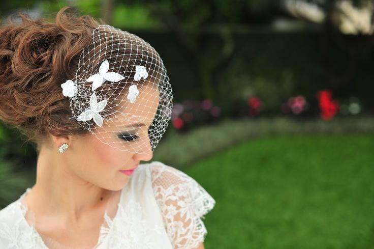 Voilette Fernanda para noivas tipo faixa com aplicação de delicadas rendas bordadas com vidrilhos, R$ 160,00. Em um lindo penteado com coque.  Brinco Gloria, de prata em formato de flor com detalhe de pérola natural. R$ 280,00.