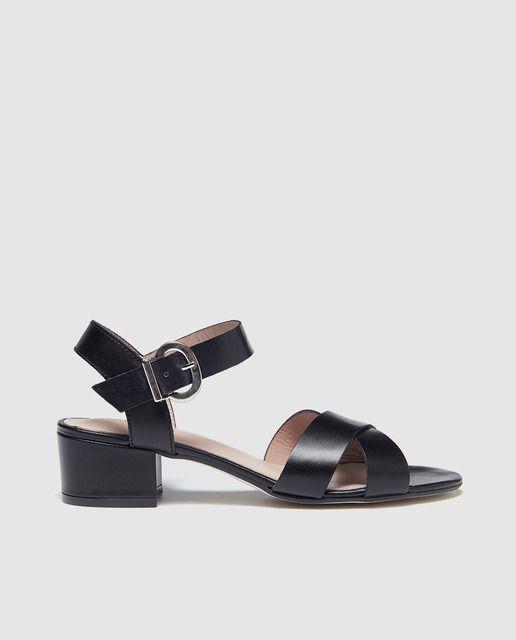 Sandalias de tacón con tiras cruzadas en  piel negro, pulsera con cierre de hebilla y tacón ancho con altura de 4 cm.