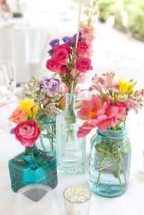 bright flowers in mixed bottles jars