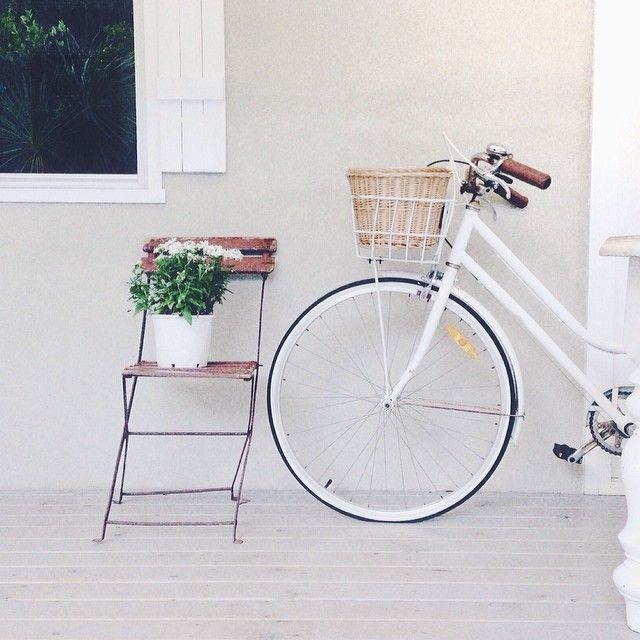 white coastal bike and shabby basket with old french vintage cafe chair and white flowers on the deck xo