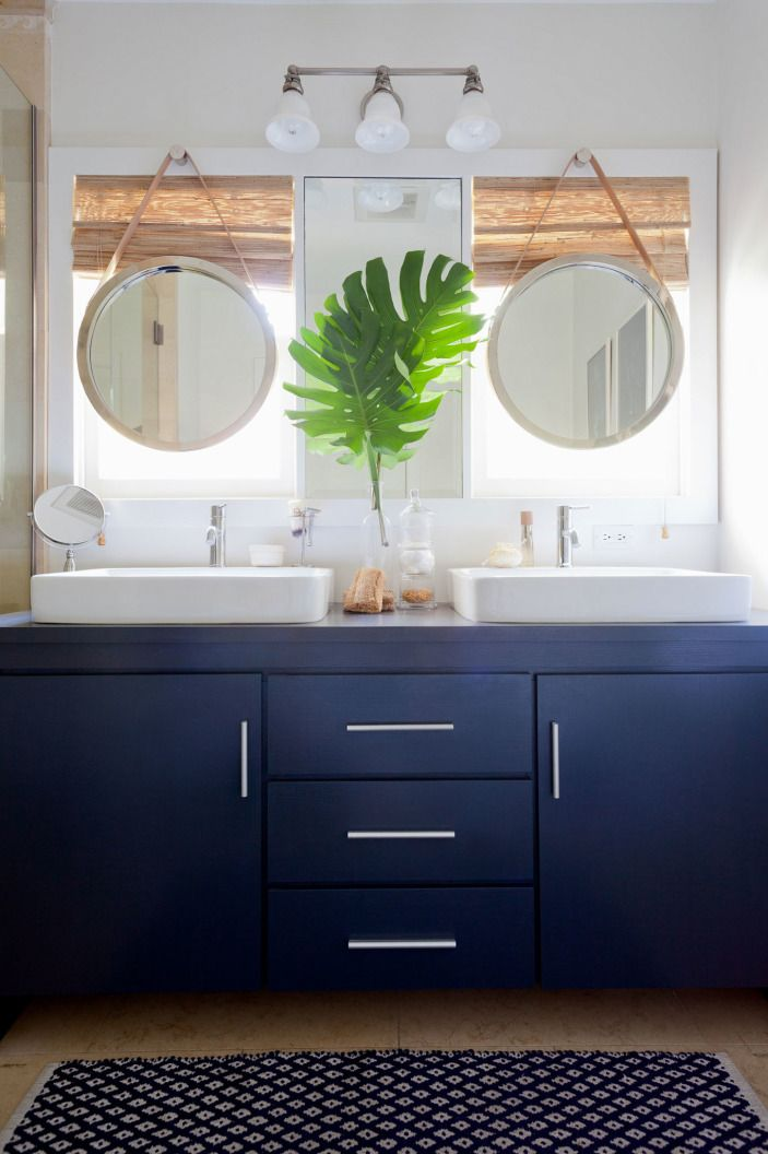 """And Jordan completely overhauled the bathroom with a brand new navy vanity and matching <a href=""""http://www.lampsplus.com/products/jamie-young-leather-strap-19-inch-high-round-wall-mirror__u3447.html"""" target=""""_blank"""">porthole mirrors</a>."""
