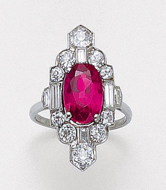 RUBY AND DIAMOND RING, 1920S.  Set with an oval ruby, bordered by circular-cut and baguette diamonds, mounted in platinum