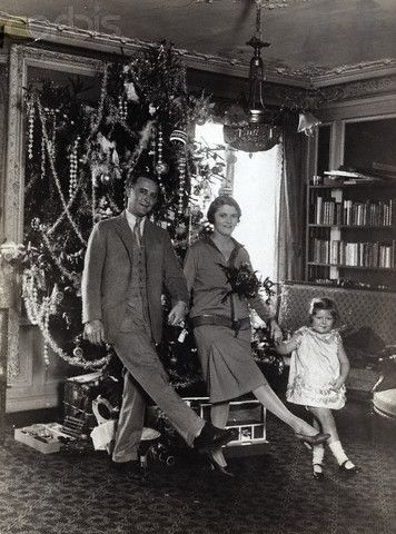 Scott, Zelda, and Scottie Fitzgerald doing kick step in front of Christmas tree. Circa 1920s