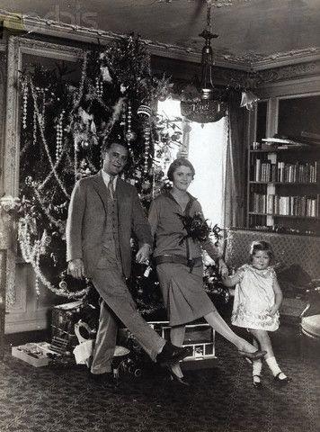 Scott, Zelda, and Scottie Fitzgerald doing kick step in front of Christmas tree. Circa 1920s