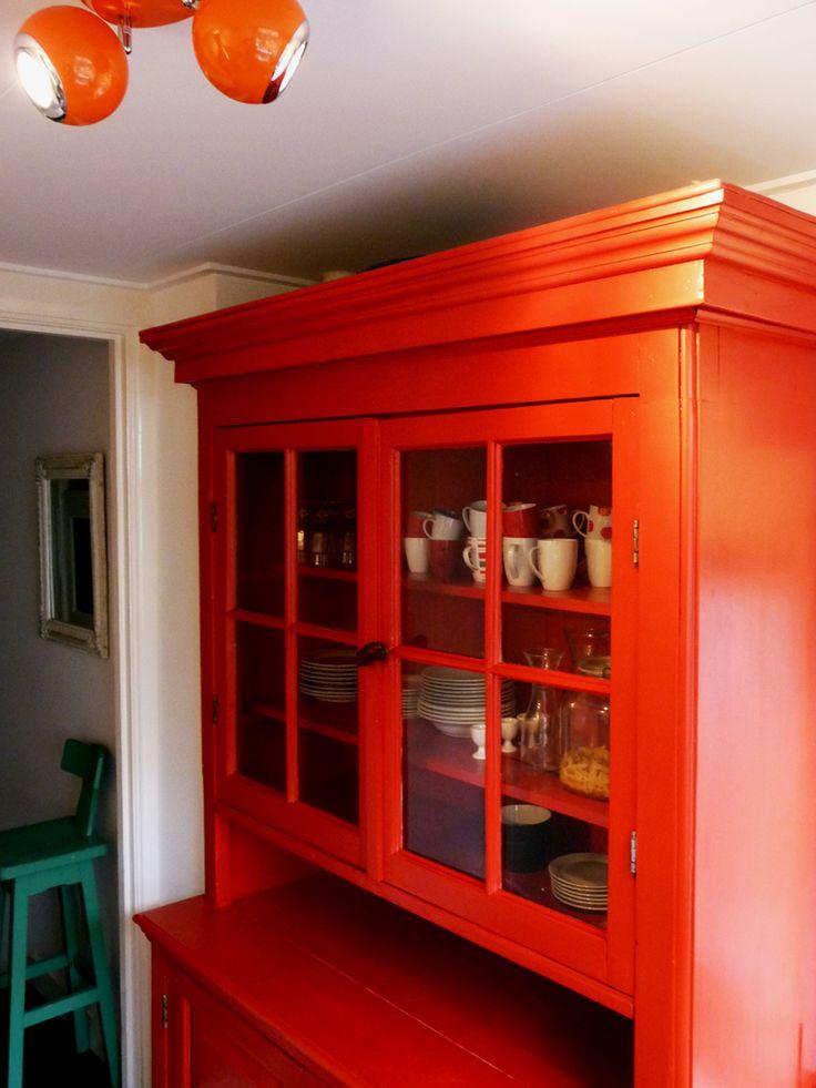 Deze rode buffetkast heeft een klassieke en landelijke stijl. Dit zie je terug aan de decoratieve elementen en de kroonlijst. Door het houtwerk van de kast vuurrood te schilderen heeft het meubel een moderne uitstraling. De originele buffetkast heeft Timmerbedrijf Schinkel gerestaureerd en op maat gemaakt voor haar nieuwe bestemming.
