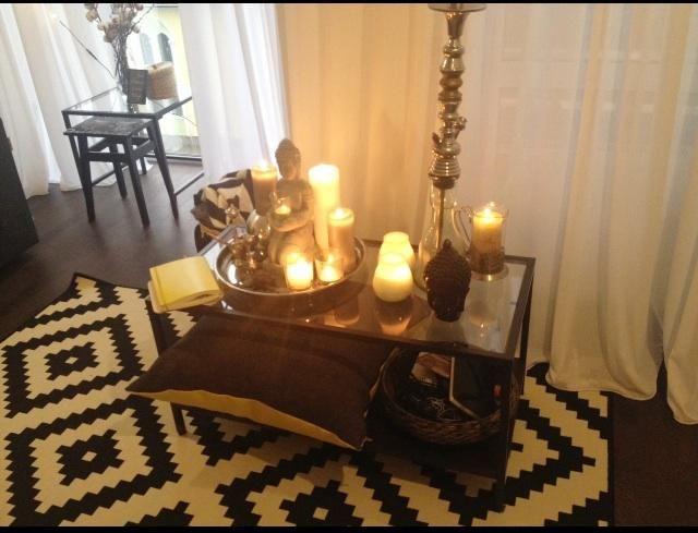 Черно-белый ковер в гостиной, композиция из свечей в интерьере