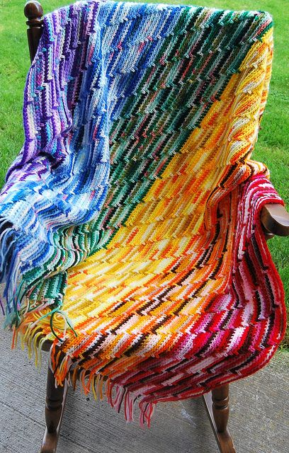 Scrappy Rainbow Blanket: Made totally from recycled and scrapped leftover yarns!  A very old design mother taught me:sc tbl, spike stitch every ten st, self fringing...work only on right side.