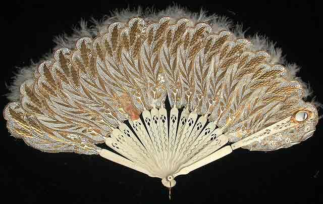 "Punched Paper and Feather Fan with Mirror, French, 1863. Paper, ivory, feathers, glass. The reason for the embossed golden wheat image is not known, but historically the wheat motif symbolized the ""golden wealth"" provided by Mother Earth. The fan's mirror made it possible for its owner to see discretely who was behind her."