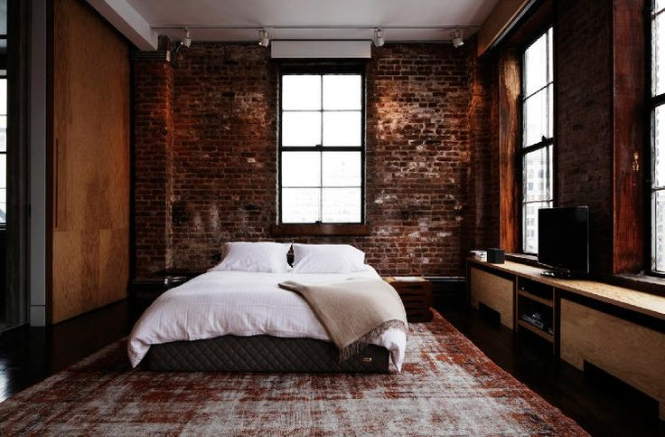 Exposed brick in old buildings is one of the quickest ways to bring the original character of a building into a room as is demonstrated here with an old rug and simple bed