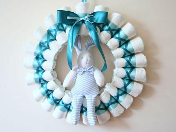 Você pode fazer uma guirlanda de fraldas para decorar a sua porta de forma diferente neste final de ano ou então para decorar a porta da maternidade de uma