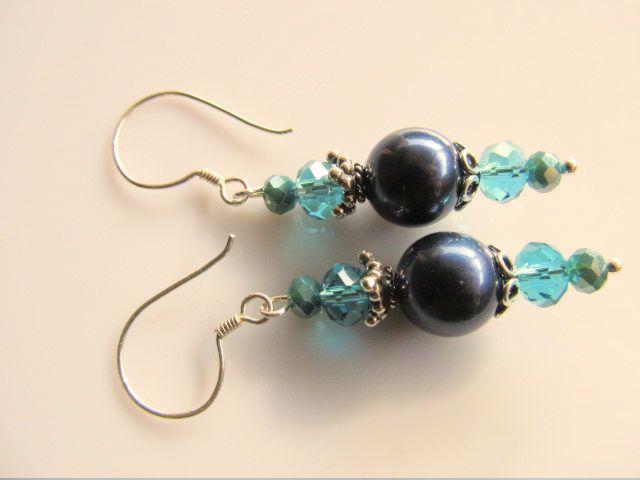 Oorbellen Hasna donkerblauwe swarovski parel met kristalglas rondellen in blauw en groen. geheel zilver