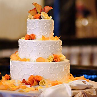 Brides: Wedding Cake with Swirls and Flowers. The buttermilk wedding cake is filled with cr�me br�l�e and cream cheese and garnished with a swirl of mango coulis. Fresh flowers add a touch of fall flair.