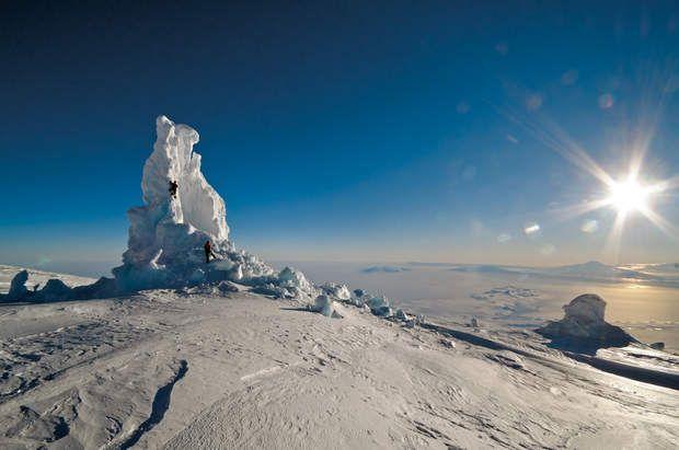 Tour de glaceÀ minuit, la lumière demeure si vive que nous avons du mal à arrêter l'exploration des tours de glace. Celle-ci est l'une des plus grandes du mont Erebus. Le flux humide et chaud venant du sous-sol en a fait s'effondrer tout un pan. Au loin, au-delà d'une autre tour de glace, la péninsule de Hut Point s'avance en direction du mont Discovery.