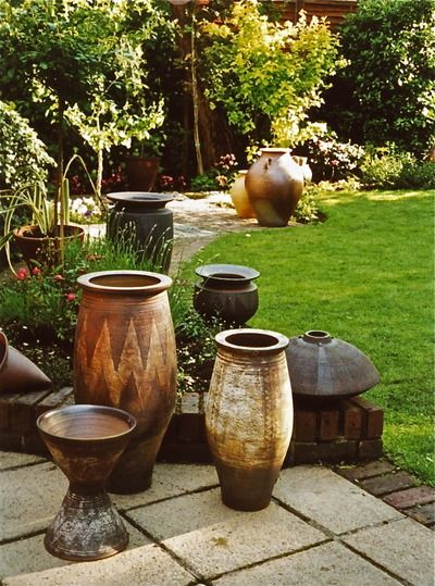 A group of three African inspired decorated planters with sgraffito decoration in the foreground, with a large Ali Baba planter at the top of the image. A group of three Jenifer Jones black pots partially visible on the low brick wall.