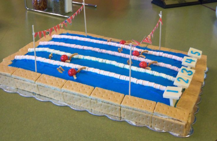 Swim Team party cake. Graham crackers for pool deck. Smarties for lane lines. Gumballs and pretzels for swimmers. White chocolate squares for starting blocks. (Flags made out of paper and not edible)