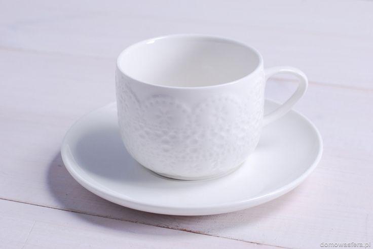 Biała filiżanka z motywem koronki, w zestawie talerzyk. Idealny pomysł na stylowy prezent dla osoby, która uwielbia kawę lub herbatę.