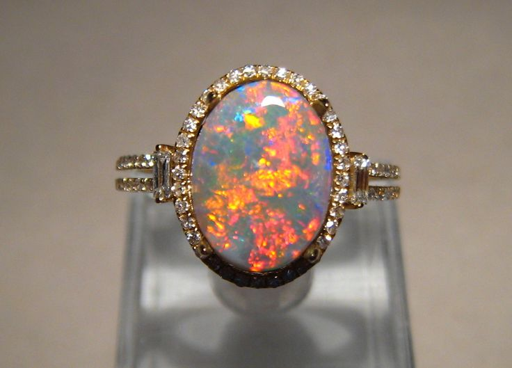 A fiery opal ring with a semi black opal accented with multi diamonds in 14k gold #opalsaustralia