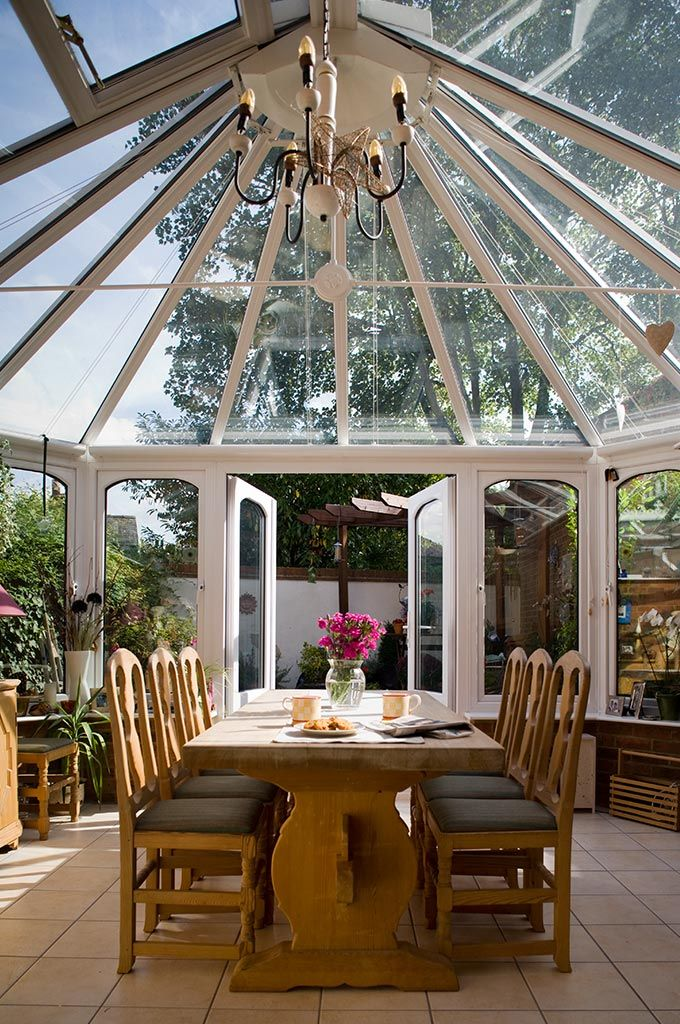 Inside A UPVC Conservatory With Dining Table And Open Doors
