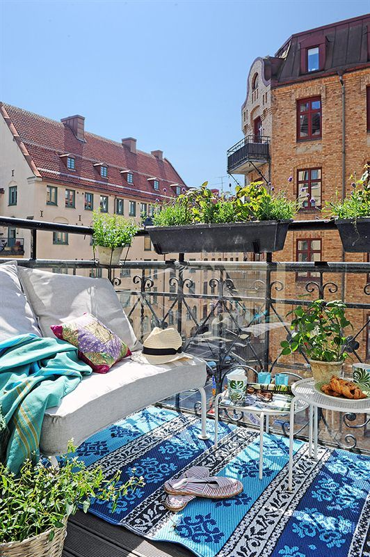 a tiny city balcony with blue outdoor mat rug aqua throw and simple white furniture.  a little boho, a little eclectic, fresh and happy
