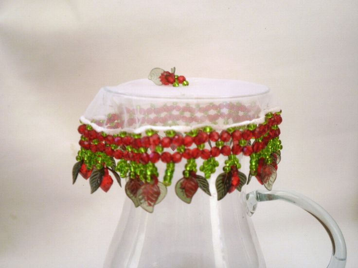 Cobre jarras com tecido em organza de 25 cms bordado com pedras acrílicas, miçangas de cristal e morango na ponta. O bordado mede mais cerca de 6 cms.    São 2 opções: transparente com miçanga vermelha ou vermelho com miçanga verde.    Acima de 3 unidades, ganhe desconto de 5%.