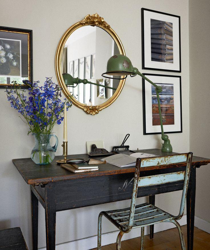 Arbetshörnan med spegel från Auktionsverket över det nötta skrivbordet. Jieldélampan ger en medveten kontrast. Liksom den turkosa industristolen från Garbo.