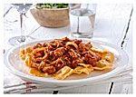 Kook de ravioli volgens de aanwijzingen op de verpakking. Giet de ravioli af. Pel de uien en snijd ze in smalle ringen. Verdeel de tonijn in stukjes. Verhit de olie van de tonijn in een ruime koekenpan en bak hierin de uiringen 4 min. op een vrij hoog vuur. Schep het mengsel regelmatig om. Verwarm de Bertolli pastasaus pittig in een andere pan. Voeg de tonijn toe en verwarm deze 2 min. mee. Hak ondertussen de peterselie fijn. Roer de helft van de peterselie door de saus. Verdeel de ravioli…